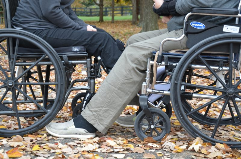 A couple face each other while using their wheelchairs