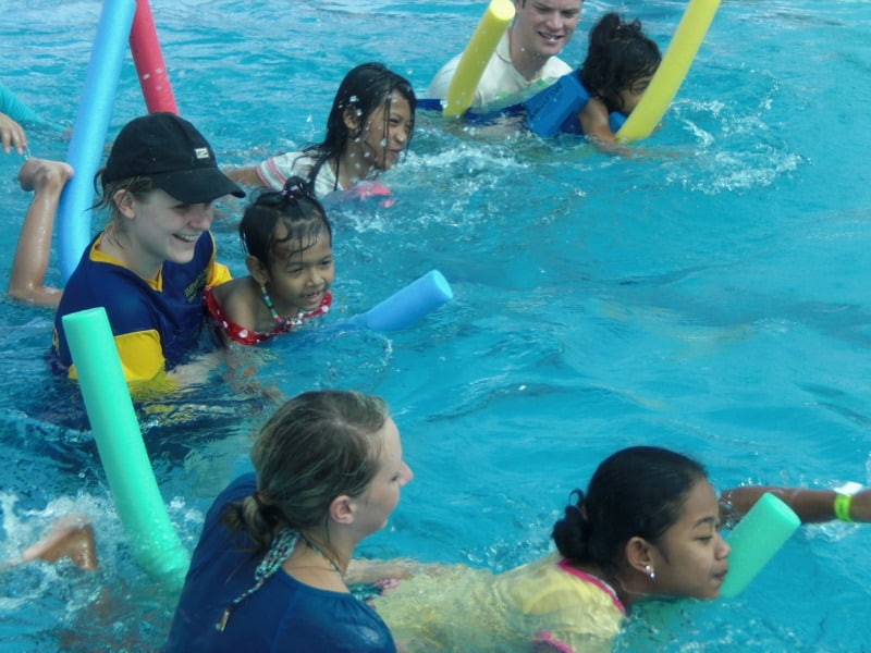 Parents helping children in pool class