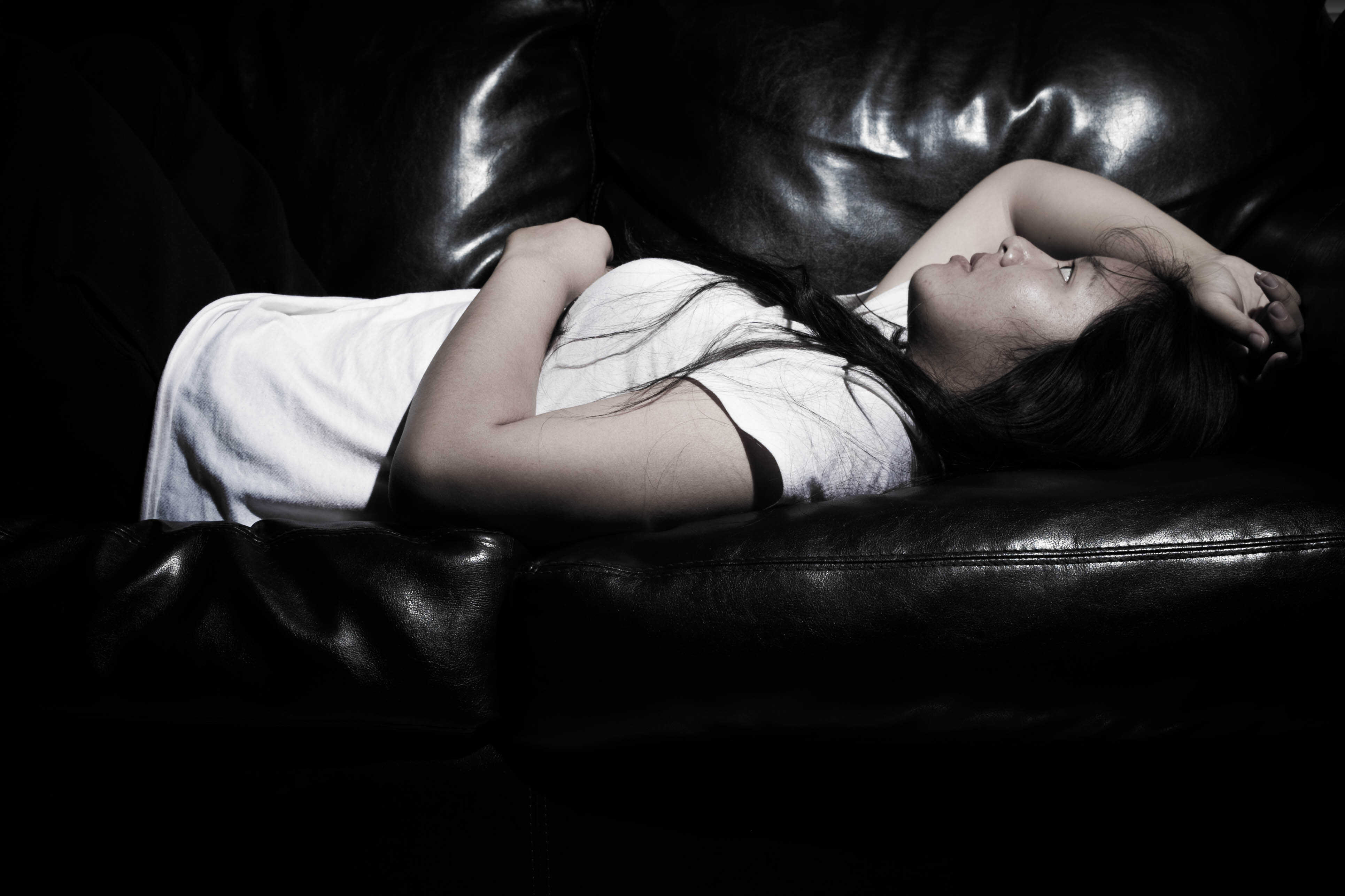 Woman resting on coach from mental exhaustion
