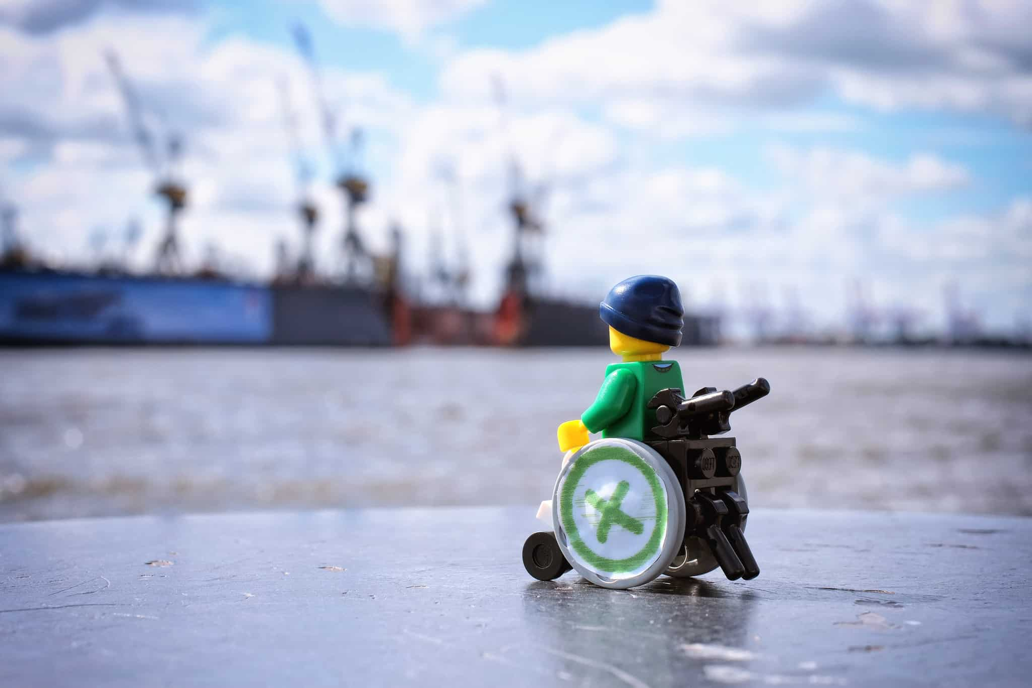 Lego figure of man in wheelchair looking out at ships by the dock