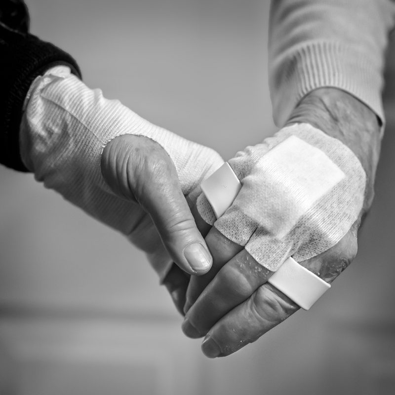 Two people holding hands after receiving treatment